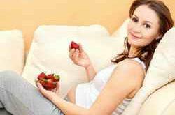 Беременная девушка ест клубнику
