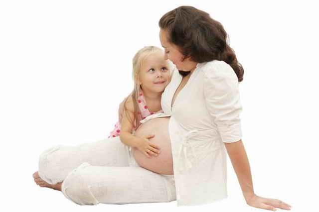 Девочка обнимает живот беременной мамы
