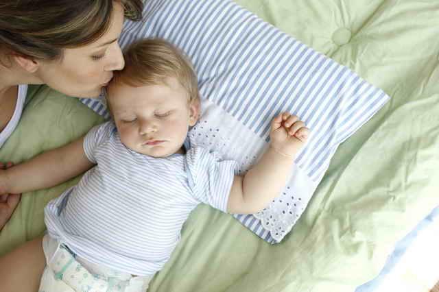 Мама целует спящего ребенка
