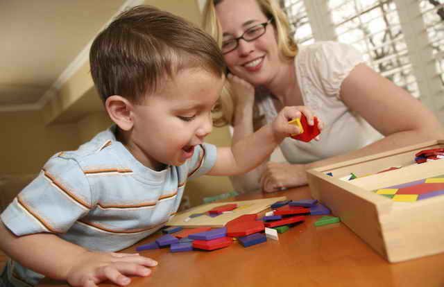 Ребенок собирает деревянные фигурки