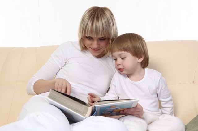 Мама читает книгу ребенку