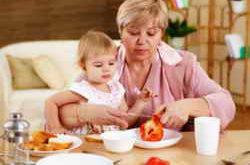 Бабушка кормит ребенка