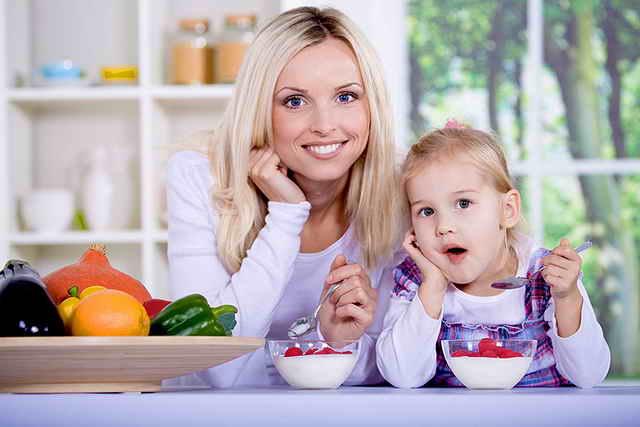 Мама и дочь едят клубнику