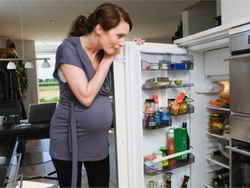 Беременная девушка около холодильника