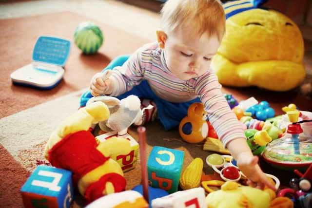 Малыш играет с игрушками