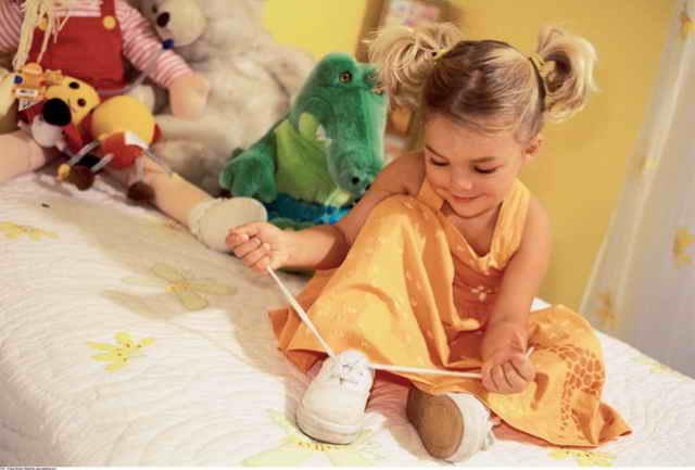Девочка шнурует ботинки