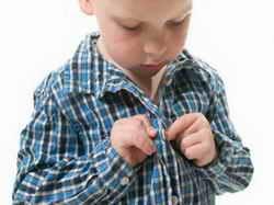 Ребенок застегивает рубашку