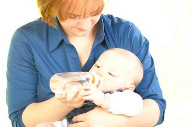 Мама поит ребенка водой